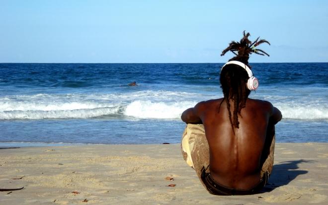Man on beach with headphones - Photo by Raíssa Viza