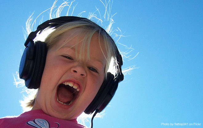Young girl listening on headphones in sunshine