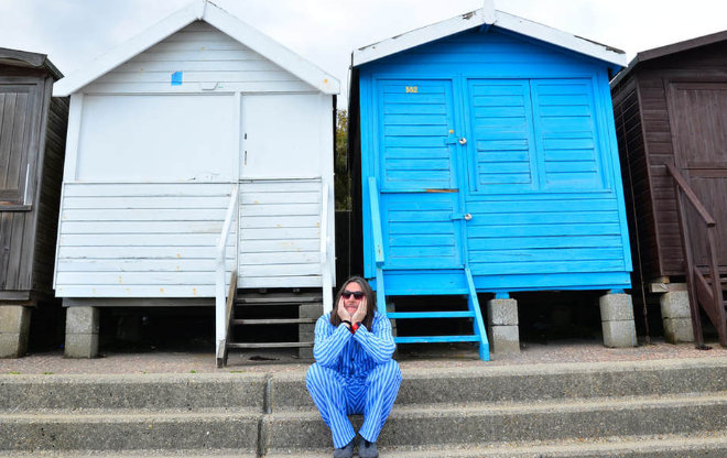 Johnno Casson sitting in front of beach huts in his pyjamas