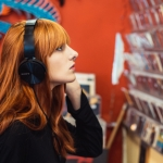 Woman listening to music on headphones in record shop