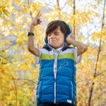 Boy in woods listening on headphones doing ROCK pose with comical expression