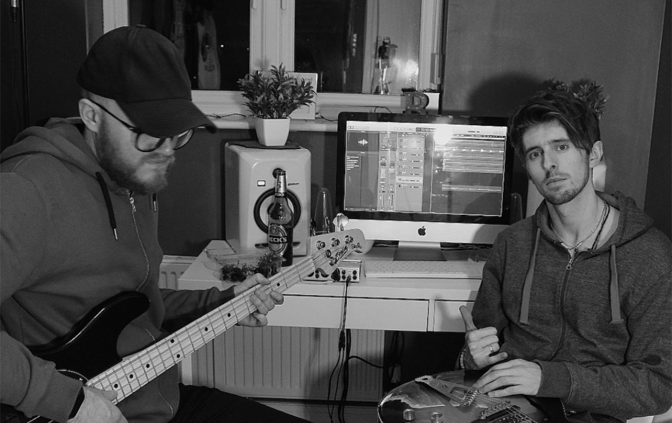 Bad Money duo sitting in front of a Mac holding guitars