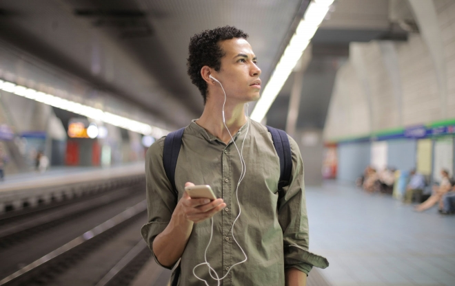 Man in train station wearing headphones