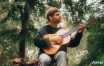 Ajimal playing guitar while sitting on a branch in the forest