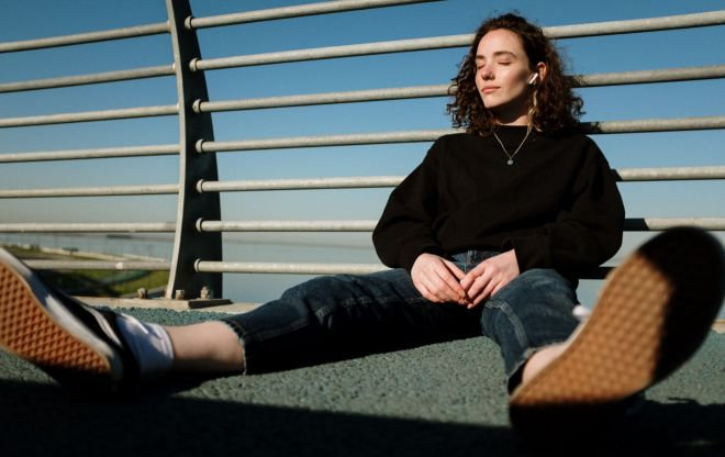 Woman wearing headphones, jeans and hoodie sitting on pavement