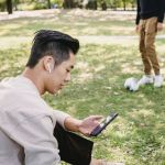 Man with smartphone and earphones in park