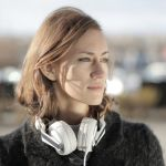 Woman with headphones presumably about to put them on and listen to the Listening Post