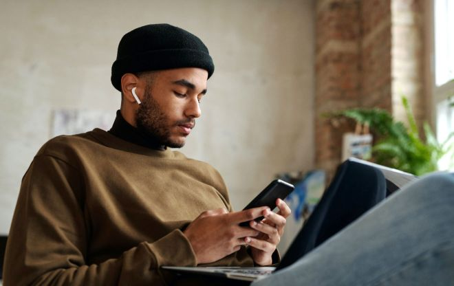 Man with AirPods, smartphone and laptop