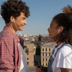 Couple sharing earbuds