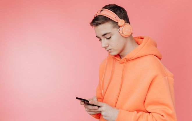 Man wearing headphones while using mobile phone